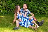 stock photo of amputee  - Loving couple sitting on the grass looking affectionately into each others eyes the man wearing a prosthesis after a leg amputation - JPG