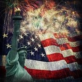 stock photo of statue liberty  - Composite photo of the statue of Liberty with a flag and fireworks in the background - JPG