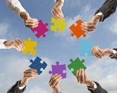 stock photo of union  - Concept of teamwork and integration with businessman holding colorful puzzle - JPG