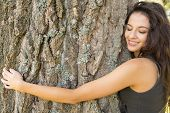 Casual gorgeous brunette embracing a tree with closed eyes in a park on a sunny day