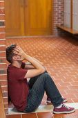 Unhappy handsome student covering his face in school
