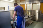 Kitchen porter washing up at sink in professional kitchen