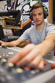 Handsome focused radio host moderating turning up volume in studio at college