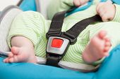 Little baby child fastened with security belt in safety car seat
