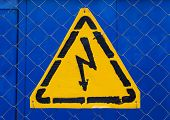 High Voltage Yellow Sign Mounted On Blue Metal Rabitz Grid