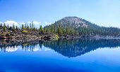 Clear reflection of Wizard Island in the Sapphire Blue Waters of Crater Lake, Oregon