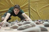 Determined young man climbing up climbing wall