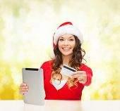 christmas, x-mas, online shopping concept - woman in santa helper hat with gift box, tablet pc compu