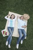 Couple lying on picnic blanket.
