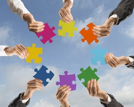 stock photo of merge  - Concept of teamwork and integration with businessman holding colorful puzzle - JPG