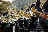 stock photo of trombone  - Trombone line of marching band with instruments up - JPG