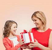 family, child, holiday and party concept - smiling mother and daughter with gift box