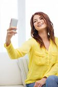 home, technology and internet concept - smiling woman with smartphone sitting on couch at home