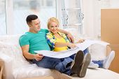 moving, home and couple concept - smiling couple relaxing on sofa and looking at blueprint in new ho