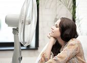 home technology concept - happy and smiling woman sitting near ventilator