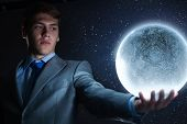 Young man in suit holding moon in palm