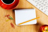 Cup of coffee notepad and keyboard on wooden table