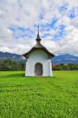 Small rural chapel on a green meadow. Picturesque forged door decorated rows of round rivets. Bright