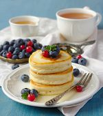 Stack Of Pancakes With Fresh Berries And Honey