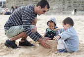 Father And Children Building Sandcastle
