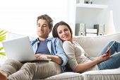 picture of peeking  - Young couple relaxing on sofa with digital tablet and laptop - JPG