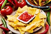 stock photo of nachos  - plate of nachos with salsa on wooden table - JPG