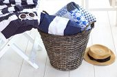 Wicker clothes basket with patchwork quilt and a pillow inside