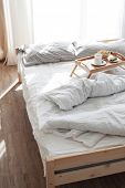Wooden tray with coffee and breakfast on the bed