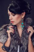 Young woman in a fur coat in  earrings