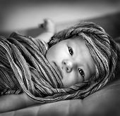 Black and white photo of cute little baby girl wrapped in scarf, lying down on the bed, kids fashion concept