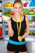 Healthy woman with fresh salad standing near open fridge full of vegetables, athletic girl with meas