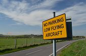 No parking low flying aircraft sign.