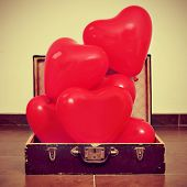 a pile of red heart-shaped balloons in an old suitcase, with a retro effect