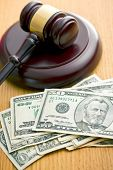 judge gavel and dollars on wooden table