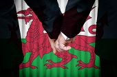 picture of same sex marriage  - Two gay men stand hand in hand before a marriage altar featuring an overlay of the flag colors of Wales - JPG