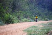 stock photo of riding-crop  - young man riding mountain bicycle on dusty road use for helathy and cyclist activities - JPG