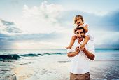 Healthy loving father and daughter playing together at the beach at sunset Happy fun smiling lifesty