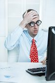Businessman with a red tie and a blue shirt has made a mistake - touching his head at desk with his computer.