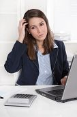 Pensive young businesswoman at desk - unhappy and bored