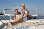 Two business people working with laptop on a sailing boat - sailing trip.