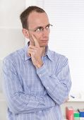 Man with glasses touching chin and skeptical at Office.