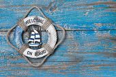 Welcome on board - lifebuoy blue wooden background