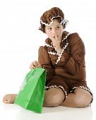A barefoot elementary gingerbread girl gesturing shh! while preparing to peek into a green gift bag.  On a white background.