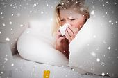 Composite image of blonde woman sneezing against snow falling