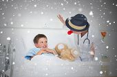 Doctor entertaining sick boy in hospital bed against snow falling