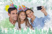 Woman taking pictures of her family during a birthday party against snow
