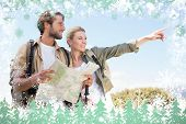Attractive hiking couple reading the map on mountain trail against snow