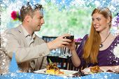 Composite image of cheerful couple having dinner together against snow