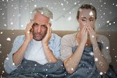 Composite image of sick couple sitting on the couch under a blanket against snow falling