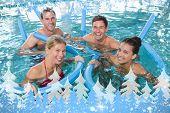 Happy fitness class doing aqua aerobics with foam rollers against snow